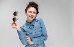 Muchacha morena joven que sostiene los vidrios en su mano Vidrios del gato El pelo se recolecta en un bollo Imagen de archivo