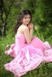 Muchacha morena joven sonriente que descansa y que se sienta en la hierba verde a Imagen de archivo libre de regalías