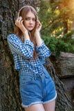 Muchacha morena linda de la mujer joven que coloca el árbol cercano en los auriculares, Fotografía de archivo libre de regalías