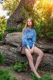 Muchacha morena linda de la mujer joven que se sienta en la piedra, luz del sol Fotografía de archivo