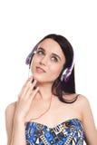 Muchacha morena linda hermosa con los auriculares en un backgrou blanco Imagen de archivo libre de regalías