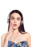 Muchacha morena linda hermosa con los auriculares en un backgrou blanco Foto de archivo