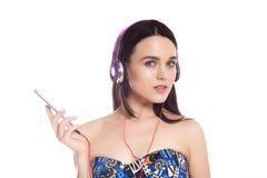 Muchacha morena linda hermosa con los auriculares en un fondo blanco, lugar para el texto, Imagen de archivo libre de regalías