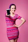 Muchacha morena linda hermosa con los auriculares en un fondo rosado Fotografía de archivo libre de regalías