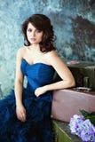 Muchacha morena muy hermosa en un vestido azul que se sienta cerca de suitca imágenes de archivo libres de regalías