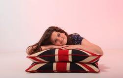 Muchacha morena que abraza la almohada Imagen de archivo libre de regalías