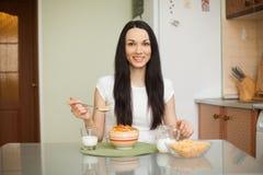 Muchacha morena que come el desayuno con leche Fotos de archivo