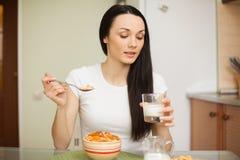 Muchacha morena que come el desayuno con leche en la cocina Fotografía de archivo