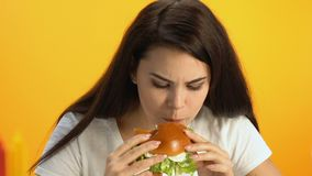 Muchacha morena que come la hamburguesa en el café, descontentado con gusto de disgusto del bocadillo metrajes