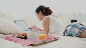 Muchacha morena que miente en cama por mañana y que charla, usando el ordenador portátil para eso Mujer joven que mecanografía en almacen de video