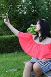 Muchacha morena que se sienta en un banco en el parque con la tableta Fotos de archivo libres de regalías
