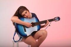 Muchacha morena que toca la guitarra azul Imágenes de archivo libres de regalías