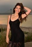 Muchacha morena sonriente atractiva en el vestido sexy negro que presenta en la playa Fotografía de archivo