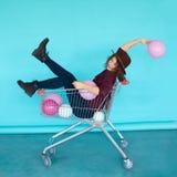 Muchacha morena sonriente de la moda que se sienta en carro de la compra Fotografía de archivo libre de regalías
