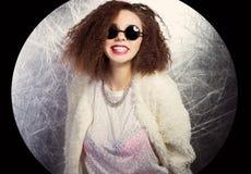 Muchacha morena sonriente feliz atractiva linda hermosa en gafas de sol redondas en el estudio en un abrigo de pieles blanco Imagen de archivo