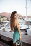 Muchacha morena sonriente hermosa con el pelo largo que presenta en yates Fotografía de archivo