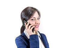 Muchacha morena sonriente joven que habla por un smartphone pH celular Imagenes de archivo