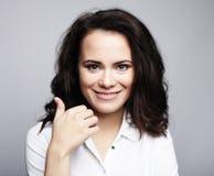 Muchacha morena sonriente linda joven sobre el fondo blanco fotos de archivo libres de regalías