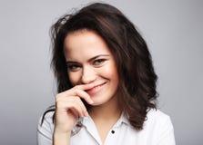 Muchacha morena sonriente linda joven sobre el fondo blanco foto de archivo