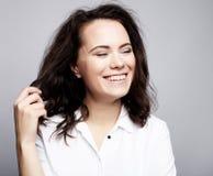 Muchacha morena sonriente linda joven sobre el fondo blanco imágenes de archivo libres de regalías