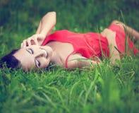 Muchacha morena sonriente que miente en hierba verde del verano Fotografía de archivo