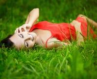 Muchacha morena sonriente que miente en hierba verde del verano Imagenes de archivo