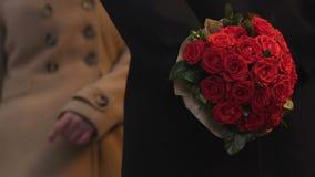 Muchacha morena tarde para la fecha, hombre que espera con las flores, dando el ramo a la mujer almacen de video