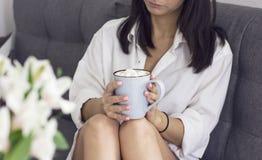 Muchacha morena triste en la camisa blanca que se sienta en el sofá con la taza en manos Imagenes de archivo