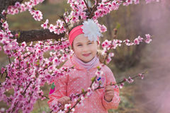 Muchacha morena vestida elegante hermosa linda con la mamá de la madre que se coloca en un campo del árbol de melocotón joven de  Fotografía de archivo