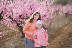 Muchacha morena vestida elegante hermosa linda con la mamá de la madre que se coloca en un campo del árbol de melocotón joven de  Imagen de archivo