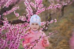 Muchacha morena vestida elegante hermosa linda con la mamá de la madre que se coloca en un campo del árbol de melocotón joven de  Fotos de archivo libres de regalías