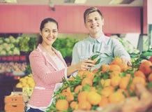 Muchacha morena y frutas cítricas de compra sonrientes del novio Fotografía de archivo