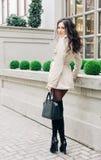 Muchacha morena zanquilarga increíble con el pelo largo, vestido en un impermeable, altas botas negras con los talones con un bol Foto de archivo libre de regalías