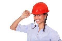 Muchacha multi-ethnic agradable en sombrero duro rojo Imagenes de archivo