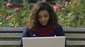 Muchacha multirracial alegre que hace la llamada video en el ordenador portátil, hablando con los amigos almacen de metraje de vídeo