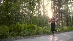 Muchacha muscular en un ejercicio corriente El atleta joven hermoso enganchó a los deportes que corrían en la cámara lenta del bo almacen de metraje de vídeo