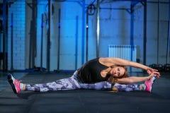 Muchacha muscular hermosa en las polainas grises que hacen estirar Se divierte el gimnasio en estilo industrial foto de archivo