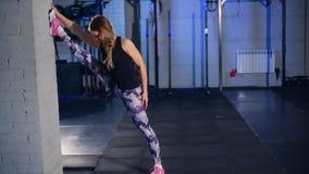 Muchacha muscular hermosa en las polainas grises que hacen estirar Se divierte el gimnasio en estilo industrial almacen de metraje de vídeo