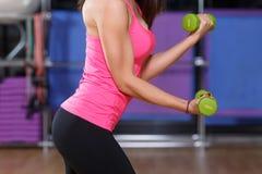 Muchacha musculosa que hace ejercicios con pesas de gimnasia verdes Foto de archivo