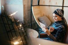 Muchacha musulmán árabe hermosa que usa la tableta en café Fotos de archivo libres de regalías