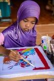 Muchacha musulmán con el batik púrpura de la pintura del hijab faric Fotografía de archivo libre de regalías