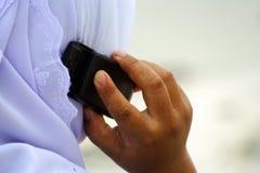Muchacha musulmán con el teléfono móvil Imagen de archivo