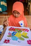 Muchacha musulmán con la tela anaranjada del batik de la pintura del hijab Fotografía de archivo libre de regalías
