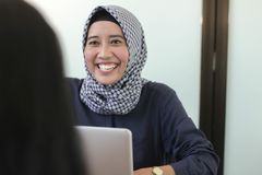 Muchacha musulmán del hijab joven profesional que trabaja con el ordenador portátil, el entrevistarse con musulmán joven de la mu fotos de archivo