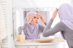 Muchacha musulmán hermosa con el problema del acné que mira en espejo Fotografía de archivo libre de regalías