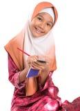 Muchacha musulmán joven con el lápiz y la libreta I Fotografía de archivo libre de regalías