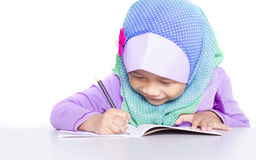 Muchacha musulmán joven que escribe un libro en el escritorio Fotografía de archivo
