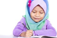 Muchacha musulmán joven que escribe un libro en el escritorio Foto de archivo libre de regalías