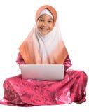 Muchacha musulmán joven que se sienta con el ordenador portátil I Foto de archivo