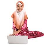 Muchacha musulmán joven que se sienta con el ordenador portátil VII Foto de archivo libre de regalías